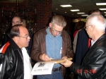 Robert Smith, Tom Brinkley, and Bob Ritz discussing a newspaper clipping about an old classmate.